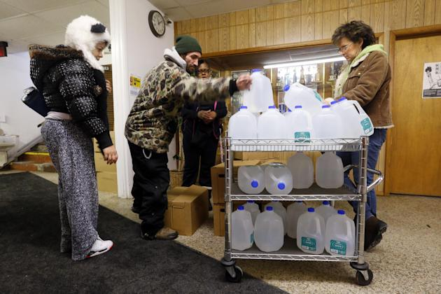 In this Feb. 3, 2015 photo, Flint residents receive free water being distributed at the Lincoln Park United Methodist Church in Flint, Mich. Since the financially struggling city broke away from the D