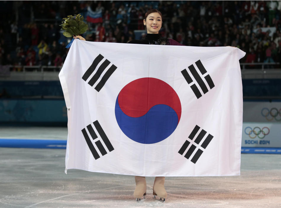 Yuna Kim of South Korea poses with the national flag as she celebrates her second place for the women's free skate figure skating final at the Iceberg Skating Palace during the 2014 Winter Olympic