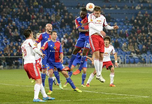 Basel's Giovanni Sio, top left, jumps for the ball with Salzburg's Stefan Ilsanker during the Europa League round of sixteen first leg soccer match between Switzerland's FC Basel and Austria's FC Salzburg at the St. Jakob-Park stadium in Basel, Switzerland, on Thursday March 13, 2014