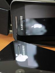 "This file illustration photo shows a Samsung phone (up) and an iPhone 4. A top Samsung executive on Monday testified that he found ""very offensive"" the suggestion that the South Korean gadget giant ripped-off Apple's market-leading mobile iPhone and iPad devices"