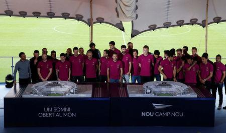 Barcelona's soccer team pose with a model of the project to reform the Camp Nou stadium in Barcelona