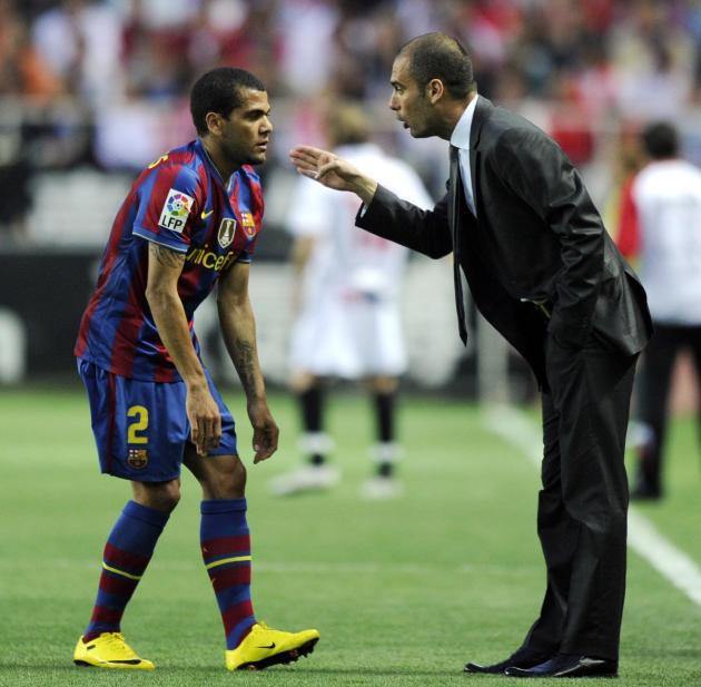 Pep Guardiola (D) habla con Dani Alves durante un partido de la liga española entre el FC Barcelona y el Sevilla, el 8 de mayo de 2010 en Sevilla