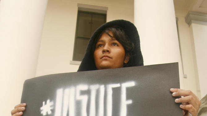 Estefania Jalvis, from Jacksonville, Fla., wears a hoodie as she holds a sign Tuesday, July 16, 2013, outside the Capitol in Tallahassee, Fla. Dream Defenders organized the sit-in of Florida Gov. Rick Scott's office in response to the 'not guilty' verdict in the trial of George Zimmerman, the Florida neighborhood watch volunteer who fatally shot Trayvon Martin, and other civil rights issues in the state. (AP Photo/Phil Sears)