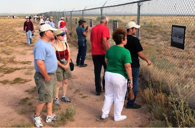 FILE - In this July 16, 2005 file photo, visitors at the Trinity Site, where the first atomic bomb was tested 60 years ago, look at historic photographs from the project at White Sands Missile Range,