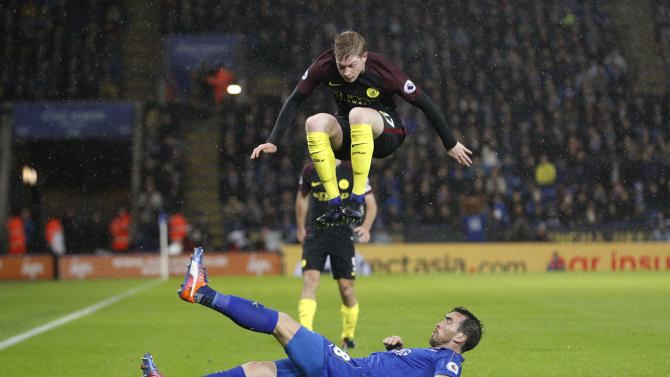 Manchester City's Kevin De Bruyne jumps over the tackle from Leicester City's Christian Fuchs