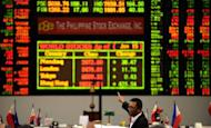 A Filipino trader points at the Philippine Stock Exchange (PSE) in Manila in June 2012. The Philippine central bank cut interest rates on Thursday for the third time this year, citing the domestic economy's need for extra help amid an uncertain global climate