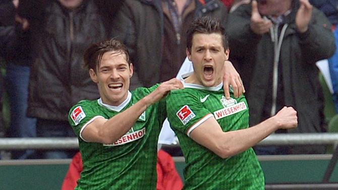 Bremen's Zlatko Junuzovic cheers with Ludovic Obraniak, left, after his  opening goal during the Bundesliga soccer  match between SV Werder Bremen and Hamburge SV  in Bremen, Germany,  Saturday March 1, 2014