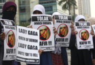 """Muslim women hold posters during a protest against Lady Gaga's concert that is scheduled for June 3, in Jakarta, Indonesia, Thursday, May 24, 2012. Lady Gaga might have to cancel her sold-out show in Indonesia because police worry her sexy clothes and dance moves undermine Islamic values and will corrupt the country's youth. The writings on the posters read """"Reject cultural invasion"""" and """"Infidel."""" (AP Photo/Tatan Syuflana)"""