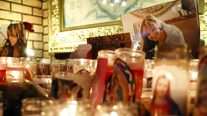Candles and pictures are displayed to pay tribute to singer Jenni Rivera at the Plaza Mexico shopping center in Lynwood, Calif., early Monday, Dec. 10, 2012. Authorities have not confirmed her death, but Rivera's relatives in the U.S. say they have few doubts that she was on the Learjet 25 that disintegrated on impact Sunday in rugged territory in Nuevo Leon state in northern Mexico. (AP Photo/Patrick T. Fallon)
