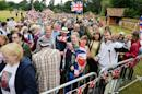 A large crowd of loyal royal fans pass through security to the area around the Church of St Mary Magdalene in Sandringham, eastern England, where Princess Charlotte will be christened in front of the Queen and close family, Sunday July 5, 2015. The church, close to William and Kate's country house Anmer Hall, is where the royal family traditionally gathers for Christmas service. It is also where Charlotte's late grandmother, Princess Diana, was christened in 1961. (John Stillwell/PA via AP) UNITED KINGDOM OUT NO SALES NO ARCHIVE