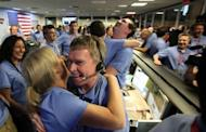 Telecom engineer Peter Ilott (C) hugs a colleague, celebrating a successful landing inside the Spaceflight Operations Facility for NASA's Mars Science Laboratory Curiosity rover at Jet Propulsion Laboratory (JPL) in Pasadena, California on August 5. Imagine taking 400 scientists on a road trip where each one wants to examine every interesting rock along the way. Welcome to the next two years