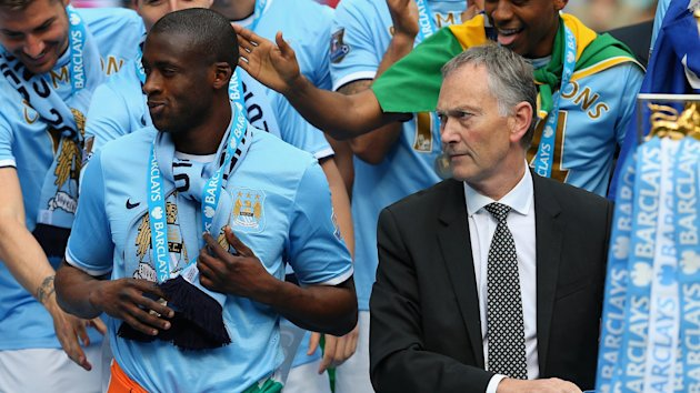 Premier League chief executive Richard Scudamore looks on as Yaya Toure of Manchester City celebrates with his team-mates