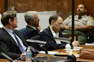 Defendant Christian Gerhartsreiter (R) sits with his attorneys Jefferey Denner (C) and Brad Bailey as they listen to the prosecutor during his murder trial at Los Angeles Superior Court on March 18, 2013. The German who posed as a Rockefeller family member after allegedly killing a man in California explained the freshly-dug soil in his back yard as plumbing work, a witness said