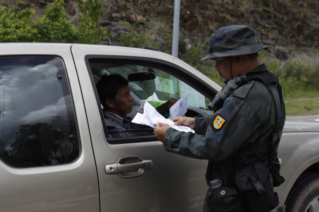 A Malaysian police officer checks travel documents at the entry point to the Malaysia-Thailand border in Wang Kelian, Malaysia on Monday, May 25, 2015. Malaysian authorities said Monday they have disc
