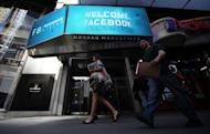 People walk past a sign welcoming Facebook at the NASDAQ stock exchange on Times Square in New York, on May 18. The spate of complaints and investigations over the Facebook stock offering suggests big institutions had an edge over small investors, raising questions about the process