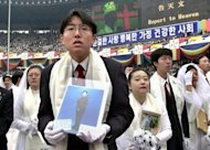 File photo taken in 2000 shows newly weds, some holding portraits of partners who couldn't attend, listening to Unification Church founder Sun Myung Moon preach during a mass wedding ceremony in Seoul. The church claims a worldwide following of three million