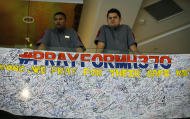 Hotel staff stand next to messages written to people involved with the missing Malaysia Airlines jetliner MH370 at a hotel in Putrajaya, Malaysia, Thursday, March 20, 2014. Four military search planes were dispatched Thursday to try to determine whether two large objects bobbing in a remote part of the Indian Ocean were part of a possible debris field of the missing Malaysia Airlines flight. (AP Photo/Vincent Thian)