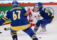 Czech hockey player Tomas Hertl (C) and Sweden's Jimmie Ericsson (R) fight for the puck during a match at the 2013 IIHF Ice Hockey World Championships in Stockholm, on May 4, 2013