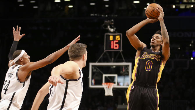 Los Angeles Lakers small forward Nick Young (0) shoots over Brooklyn Nets power forward Mirza Teletovic (33) and small forward Paul Pierce (34) in the fourth quarter of an NBA basketball game at the Barclays Center, Wednesday, Nov. 27, 2013, in New York