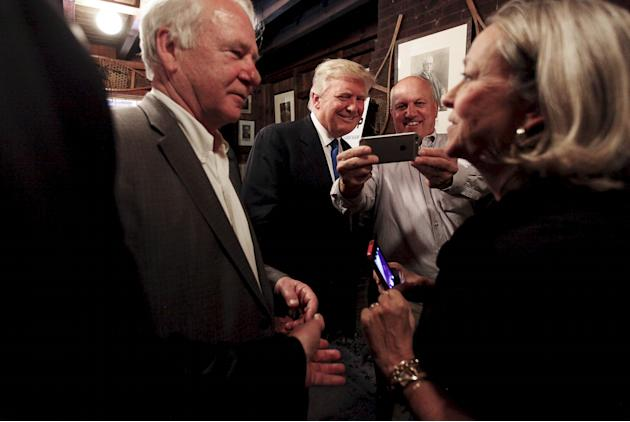 Potential Republican 2016 presidential candidate Donald Trump takes a photograph with Stephen Duprey after speaking at the Snow Shoe Club in Concord