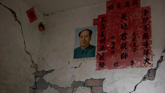 A portrait of Mao Zedong near writing commemorating Chinese ancestors is displayed on a wall damaged by Saturday's earthquake near Shangli town in southwestern China's Sichuan province, Sunday, April 21, 2013. The powerful earthquake that struck the steep hills of China's southwestern Sichuan province left at least 160 people dead and more than 6,700 injured. (AP Photo/Ng Han Guan)