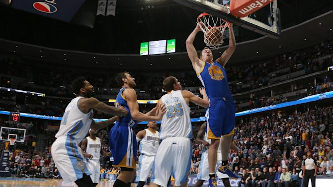 Golden State Warriors forward David Lee, right, dunks the ball for a basket as, from left, Denver Nuggets forward Wilson Chandler, Warriors center Andrew Bogut, of Australia, and Nuggets center Timofey Mozgov, of Russia, look on in the first quarter of an NBA basketball game in Denver, Monday, Dec. 23, 2013