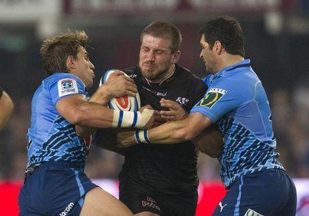 Sharks player Francois Steyn is tackled by Bulls players Wynand Olivier and Morne Steyn during their South African Super 15 rugby derby match in Durban