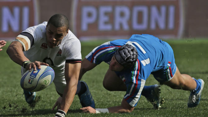 England's Luther Burrell, left, eyes the ball as Italy's Michele Campagnaro tries to stop him during a Six Nations international rugby union match between Italy and England, in Rome, Saturday, March 15, 2014. Owen Farrell accounted for 22 points and Mike Brown added two tries as England stated its case for the Six Nations title with a convincing 52-11 win over Italy on Saturday at the Stadio Olimpico. (AP Photo/Alessandra Tarantino)