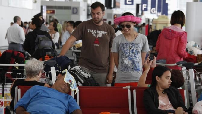 Passengers wait for their departure at Hong Kong Airport after Typhoon Usagi, the strongest storm to hit the Western Pacific this year, swiped Hong Kong