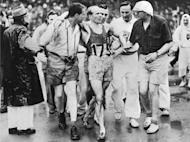 Belgium's training team supports an exhausted Gaston Reiff after he crossed in victory the finish line in the 5000 metres at Wembley Stadium during the last London Olympics in August 1948. London is the first city to host a third Olympic Games, but the modest Games of the last century were worlds away from today's glossy extravaganzas