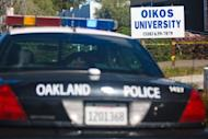 An Oakland police cruiser waits, April 4, 2012, in front of Oikos University, the scene of a shooting rampage that killed seven people, in Oakland, California
