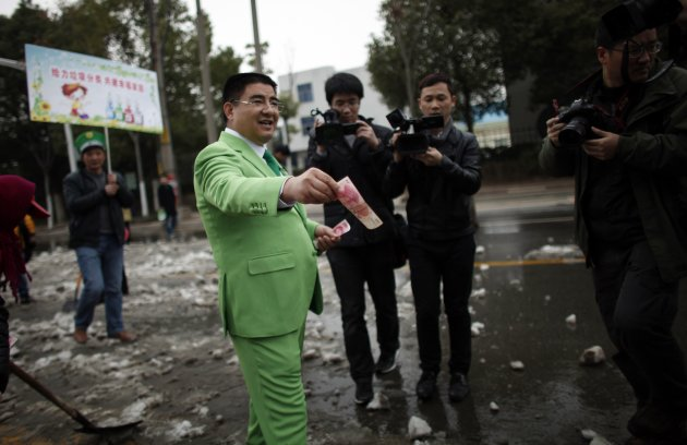 Chinese multimillionaire Chen Guangbiao gives money away to street cleaners. (Reuters)