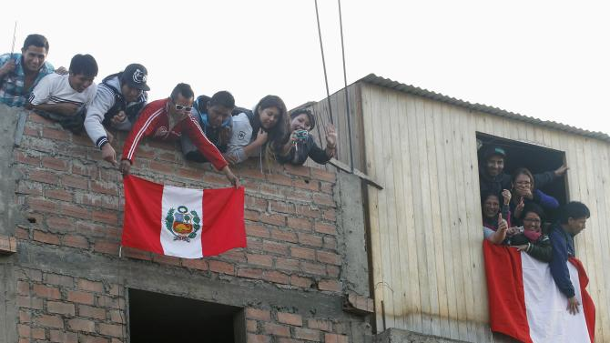 Fans of Peru's national soccer players cheer and wave Peruvian flags from a house next to the team's training session in Lima