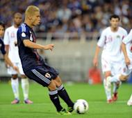 Japan's midfielder Keisuke Honda (C) kicks the ball in a penalty kick to score the team's 5th goal during their 2014 Football World Cup Asian qualifiers match against Jordan. Japan won 6-0