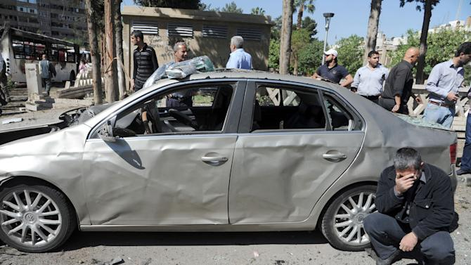 This photo released by the Syrian official news agency SANA, shows a Syrian man reacts after a car bomb exploded in the capital's western neighborhood of Mazzeh, in Damascus, Syria, Monday, April. 29, 2013. State-run Syrian TV says the country's prime minister has escaped an assassination attempt when a bomb went off near his convoy. Syrian TV says Prime Minister Wael al-Halqi was unhurt in the attack. (AP Photo/SANA)