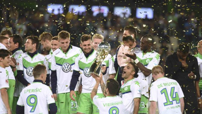 VfL Wolfsburg players celebrate with trophy after defeating Bayern Munich to win the German Supercup in Wolfsburg
