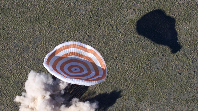 The Russian Soyuz space capsule, carrying U.S. astronaut Thomas Marshburn, Russian cosmonaut Roman Romanenko and Canadian astronaut Chris Hadfield, lands some 150 km (90 miles) southeast of the town of Dzhezkazgan in central Kazakhstan, Tuesday, May 14, 2013. The Soyuz space capsule carrying a three-man crew returning from a five-month mission to the International Space Station landed safely Tuesday on the steppes of Kazakhstan. (AP Photo/Sergei Remezov, Pool)