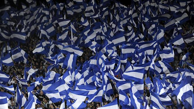 FC Porto fans wave flags on the stands prior to their 3-1 victory over Sporting in a Portuguese League soccer match at the Dragao stadium in Porto, Portugal, Sunday, Oct. 27, 2013