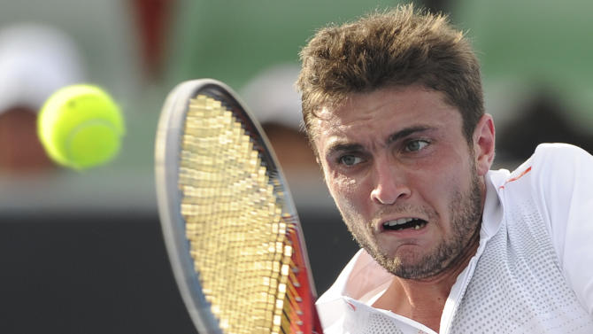 France's Gilles Simon makes a backhand return to Thailand's Danai Udomchoke during their first round match at the Australian Open tennis championship, in Melbourne, Australia, Tuesday, Jan. 17, 2012. (AP Photo/Andrew Brownbill)
