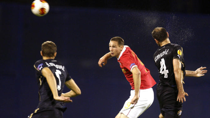Dinamo's Jozo Simunovic, left, and Dinamo's Josip Simunic jump for a ball with PSV's Tim Matavz during a Europa League group B soccer match between PSV Eindhoven and Dinamo Zagreb, in Zagreb, Croatia, Thursday, Oct. 24, 2013