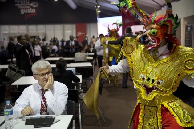 """A man attending the annual meetings by the World Bank Group and IMF watches a man perform a traditional dance from Puno, Peru called """"La Diablada"""" inside the venue's dining area in Lima,"""