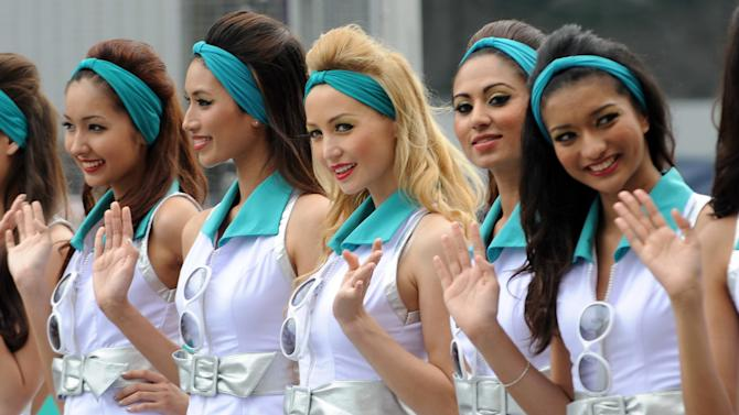 Grid girls pose for photographers during the drivers' grid introductory ceremony prior to the start of Formula One's Malaysian Grand Prix at the Sepang International Circuit in Sepang on March 25, 2012.  AFP PHOTO / ROSLAN RAHMAN (Photo credit should read ROSLAN RAHMAN/AFP/Getty Images)
