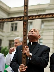 FILE - In this April 6, 2012, file photo, Rev. Wilton Gregory, the Archbishop of Atlanta holds a cross during the 32nd annual Good Friday Pilgrimage at Hurt Park in Atlanta. Gregory apologized Monday, March 31, 2014, for building a $2.2 million mansion for himself, a decision criticized by local Catholics who cited the example of austerity set by the new pope. (AP Photo/Atlanta Journal-Constitution, Jason Getz, File)