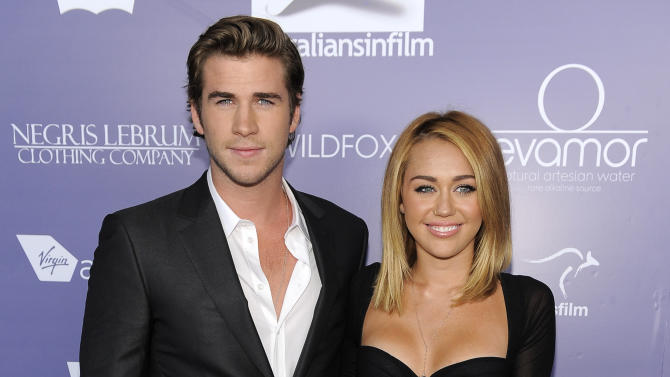 """FILE - In this June 27, 2012 file photo, actor Liam Hemsworth, left, an honoree at the Australians in Film 8th Annual Breakthrough Awards, poses with his fiance Miley Cyrus on the red carpet in Los Angeles. Representatives for both celebrities confirmed they have called off their engagement. They met on the set of 2010's """"The Last Song."""" (Photo by Chris Pizzello/Invision/AP, File)"""