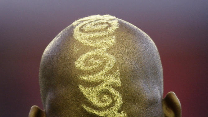 Manchester City's Mario Balotelli sports a new haircut as he takes to the pitch before his team's English Premier League soccer match against Liverpool at Anfield Stadium, Liverpool, England, Sunday, Nov. 27, 2011. (AP Photo/Jon Super)