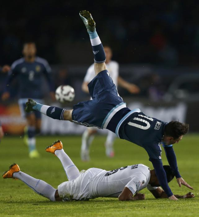 Argentina's Messi flies over Uruguay's Pereira during their first round Copa America 2015 soccer match at Estadio La Portada in La Serena