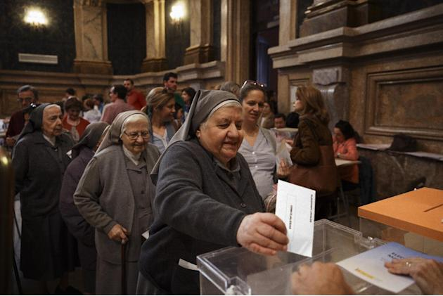 A nun casts her vote at a polling station in Madrid, Spain, Sunday, May 24, 2015. Opinion polls indicate voters are fed up with Spain's economic downturn and the corruption scandals that have rock
