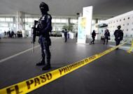 Federal police cordon off an entrance to Benito Juarez international airport Terminal 2, in Mexico City, where three police officers were shot dead on June 25, 2012
