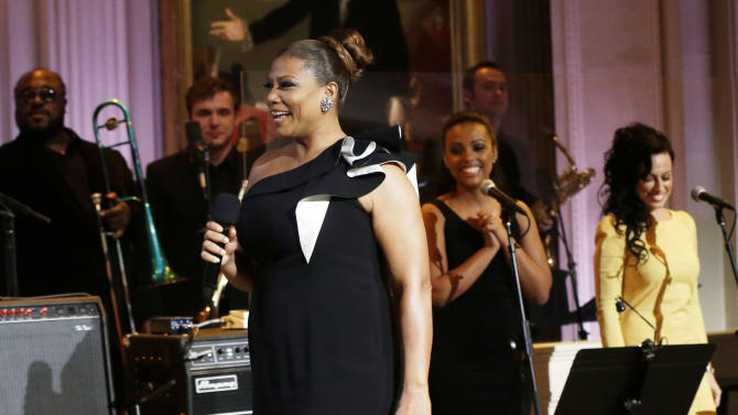 "President Barack Obama, center seated, and first lady Michelle Obama, right, look towards Queen Latifah, who speaks on stage during the ""In Performance at the White House"" in the East Room of the White House in Washington, Tuesday, April 9,  2013, a program for a celebration of Memphis Soul Music. (AP Photo/Pablo Martinez Monsivais)"