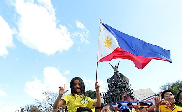 A child raises a Philippine flag and flashes the Laban (fight) sign, during the 27th anniversary of EDSA 1 People Power Revolution in Quezon City, north of Manila on 25 February 2013. EDSA People Power Revolution also known as the EDSA Revolution, or People Power) was a four-day series of non-violent mass demonstrations that toppled the Marcos dictatorship and installed Corazon Aquino as president in 1986. (Czeasar Dancel/NPPA Images)